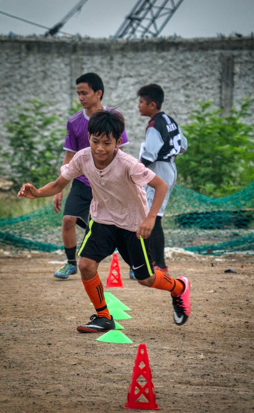 Ethnic kid running through training cones while playing football with team players on field