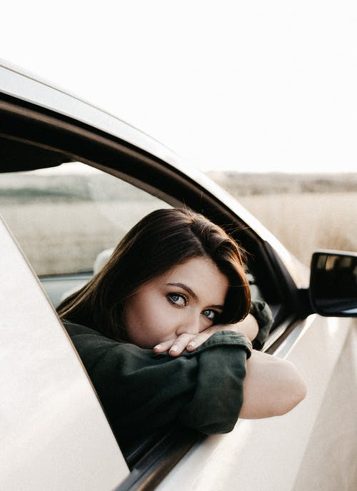 Thoughtful female with brown hair sitting in light car and looking out of window placed in nature in daytime