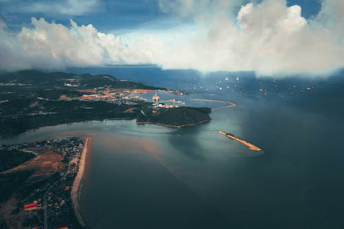 Aerial view of picturesque scenery of calm sea near island with coastal town and beach under cloudy blue sky