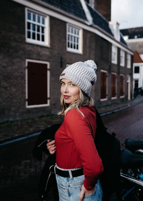Positive woman in stylish clothes standing on street near building