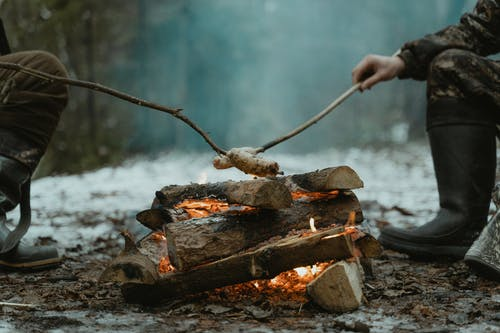Person Holding a Stick on a Wood Burning