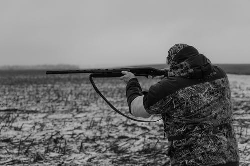 Grayscale Photo of Person Holding Rifle