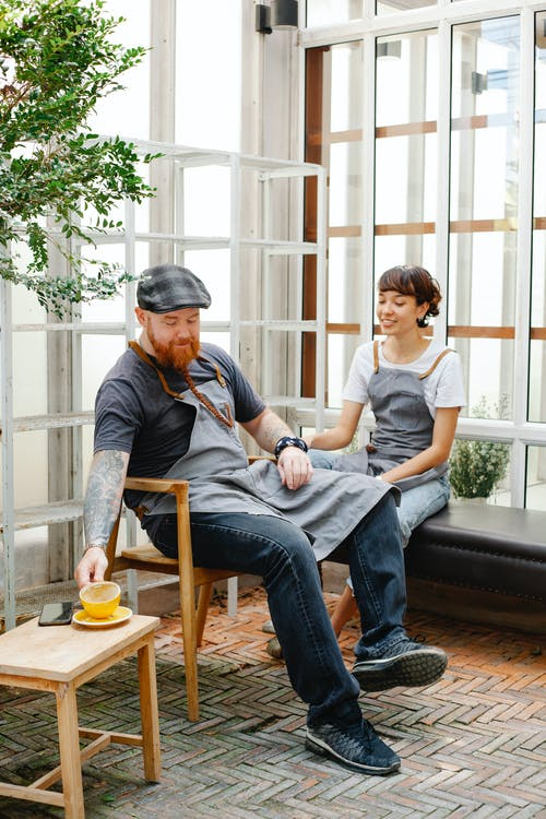 Full body of positive couple of colleagues in casual clothes and aprons sitting near glass wall and having conversation near cup of drink and phone in daytime