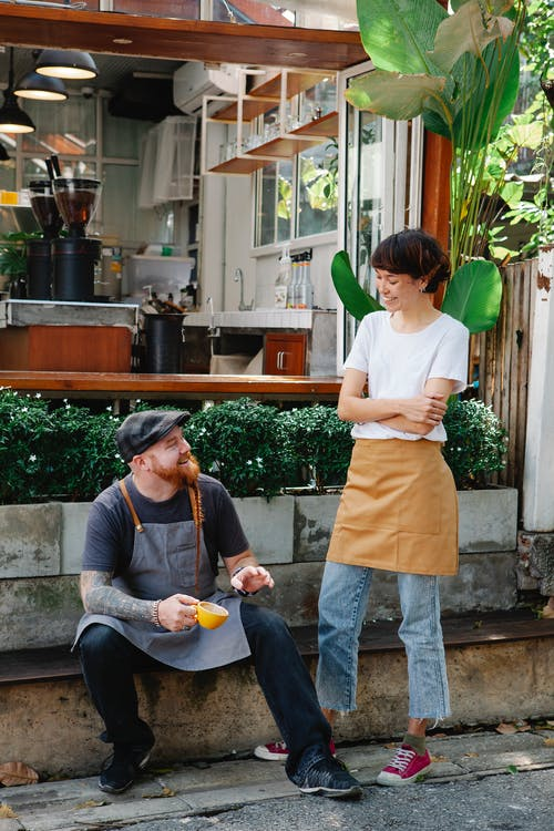 Couple of happy barista colleagues in casual clothes and aprons having conversation in street near cafeteria with cup of drink near plants in daylight and looking at each other