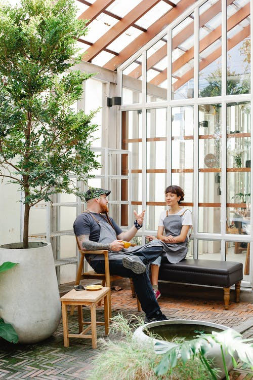 Full body couple of colleagues in casual clothes and aprons sitting near glass wall and having conversation with cup of drink near phone and potted plants in daytime