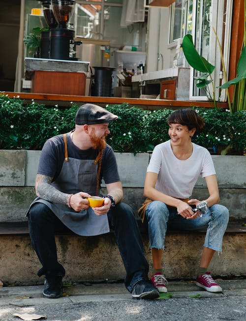 Couple of colleagues having conversation in street near cafe