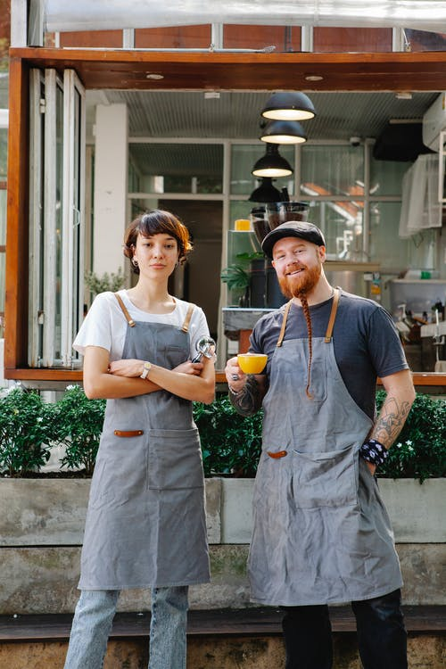 Confident couple of barista coworkers in casual outfit and aprons standing with cup of coffee and portafilter in street near plants and cafe while looking at camera