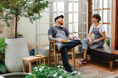 Full length of smiling couple of coworkers in casual outfit and aprons sitting near glass wall and talking with cup of drink and potted plants in day