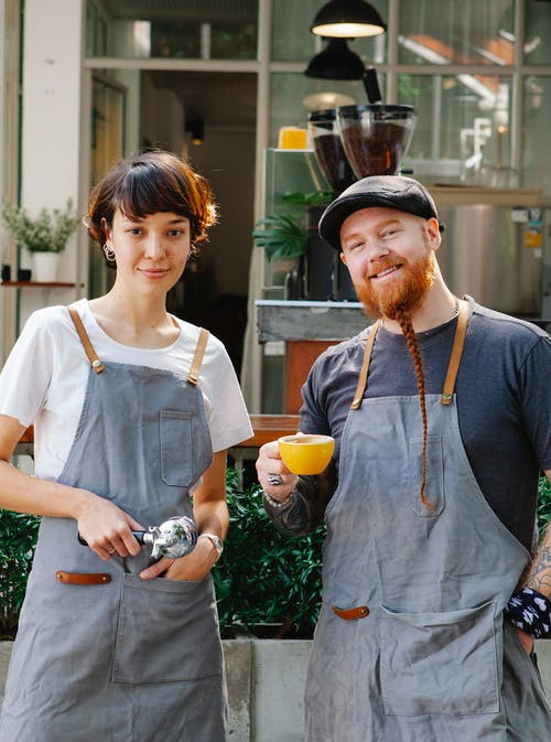 Smiling couple of barista coworkers in aprons and casual outfit spending time in street with portafilter and cup of coffee near cafeteria and plants while looking at camera