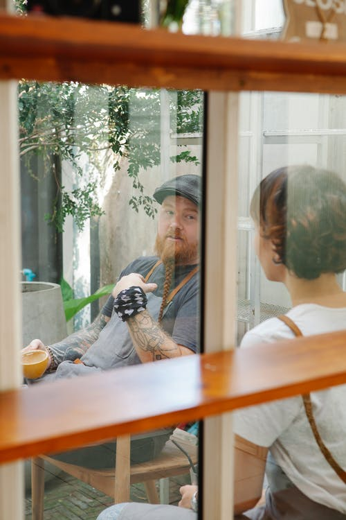 Through window of couple of coworkers in casual outfit and aprons sitting with cup of drink near potted plants while speaking in daytime