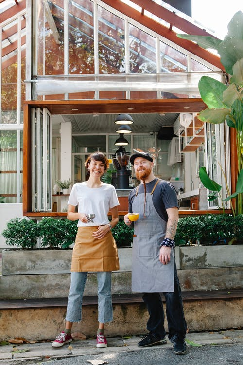 Full body couple of smiling barista colleagues in casual clothes and aprons standing with portafilter and cup of drink in street with plants near cafeteria and looking at camera