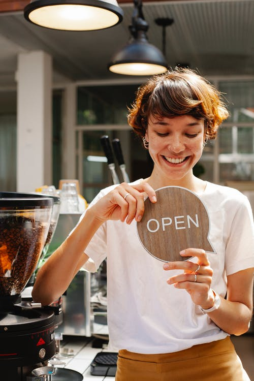 Woman standing in cafe with open sign