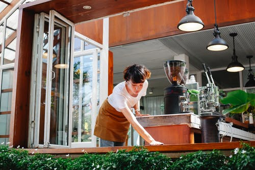 Woman worker washing bench in cafe