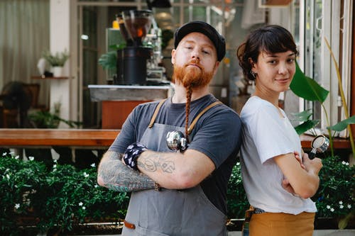 Couple of confident barista coworkers in aprons and casual outfit standing in street near cafeteria with portafilter near plants while looking at camera in daylight