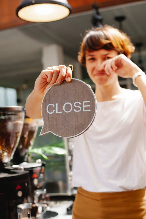 Woman standing in cafe with sign close