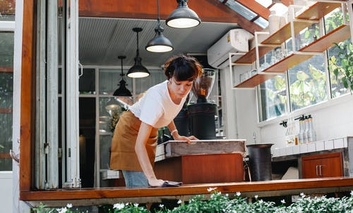 Female employee cleaning surface in cafeteria