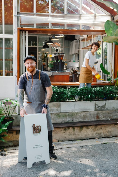 Happy couple of coworkers in aprons and casual clothes standing near signboard and watering plants near cafe in daytime and looking at camera