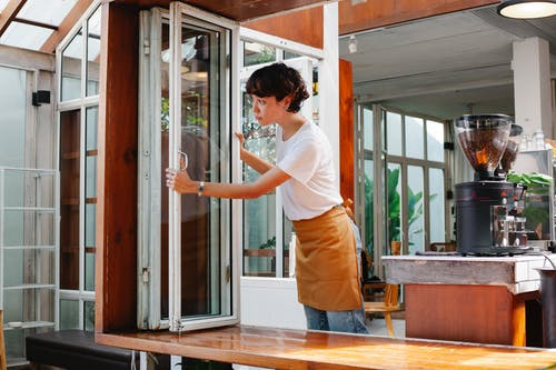 Young waitress in casual clothes and apron standing in modern cafe and looking over window in daytime