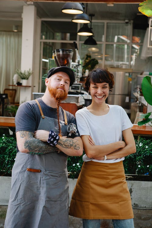 Couple of confident colleagues in casual clothes and aprons spending time in street near cafe with portafilter near plants while looking at camera in daytime