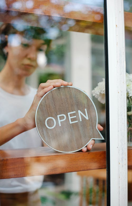 Woman with sign open in cafe