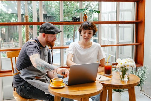 Couple of colleagues in aprons and casual clothes in cafe working on laptop at table with glass of drink and coffee cup in daylight
