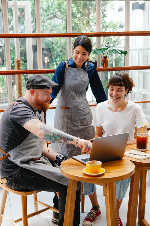 Cheerful multiethnic cafeteria staff and female barista talking at wooden tables with netbook in daylight