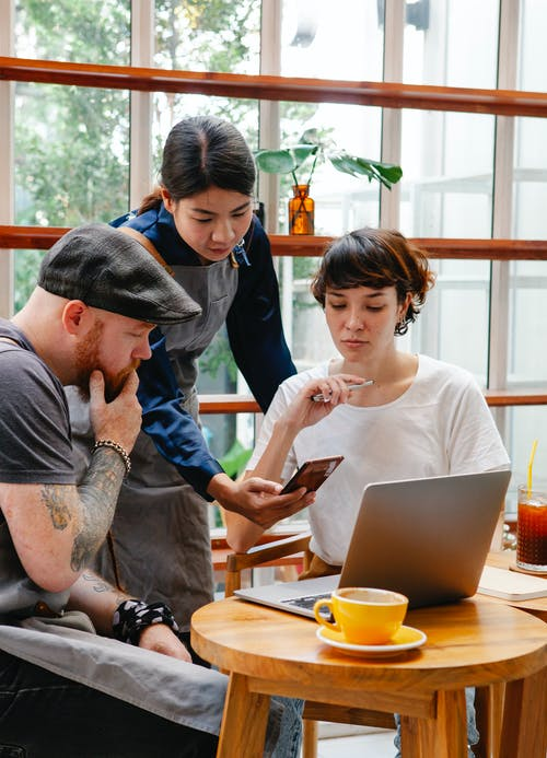 Diverse colleagues with smartphone and laptop speaking in cafe