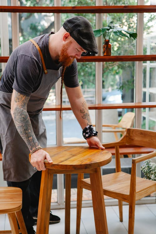 Side view of content tattooed male worker in apron putting wooden table on floor in cafeteria