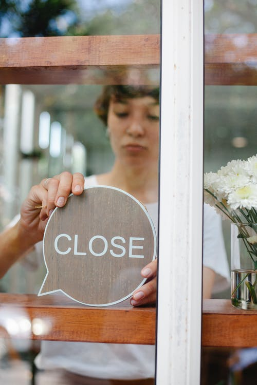 Through glass wall view of crop young cafeteria employee putting signboard with Close title on wooden beam