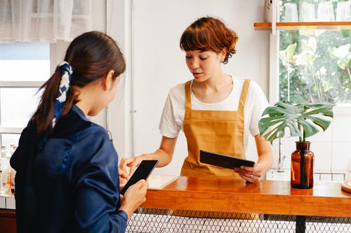 Cafe employees with tablet and smartphone speaking at counter