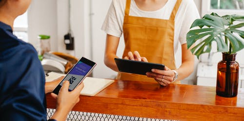 Crop anonymous female employee with application on cellphone screen interacting with partner using tablet at counter in cafeteria