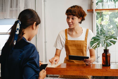 Cheerful young cafeteria worker pointing at paper while speaking with anonymous coworker with smartphone in daytime