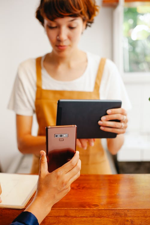 Crop worker with tablet against partner with smartphone in cafe