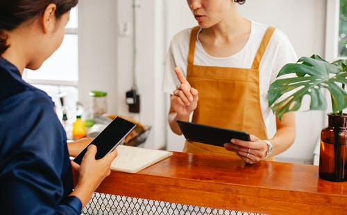 Crop anonymous female employee with finger up speaking with partner touching black screen on cellphone in cafe