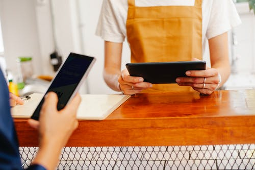 Faceless cafeteria partners using smartphone and tablet at counter