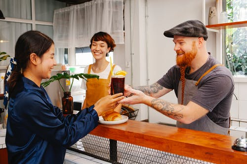 Glad hipster male employee passing glass of Black Velvet cocktail to smiling ethnic colleague at work