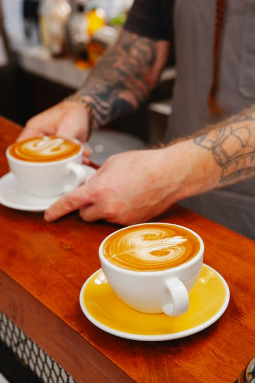 Crop unrecognizable tattooed male cafeteria employee serving cups of tasty latte with ornament on smooth froth