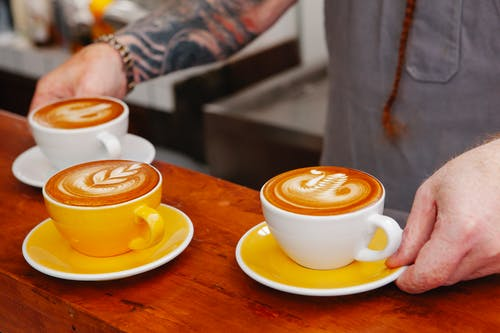 Crop barista with cups of delicious coffee in cafe