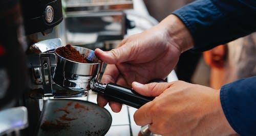 Crop barista inserting portafilter into coffee machine at work