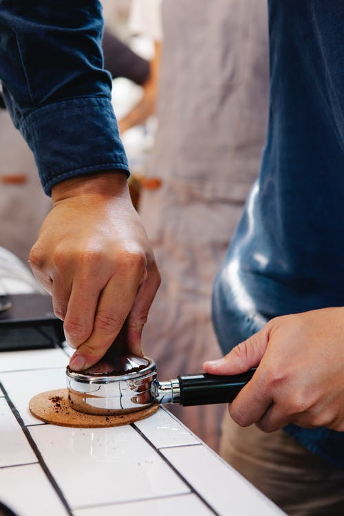 Crop anonymous male employee pressing coffee in portafilter with tamper on table in cafeteria