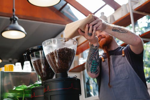 From below of tattooed male employee pouring aromatic coffee beans from paper bag into electric grinder in cafe kitchen