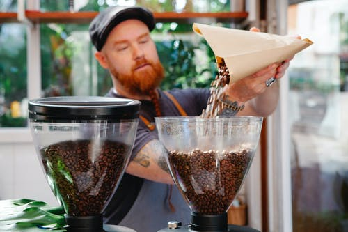Unshaven employee pouring coffee beans into grinder in cafe