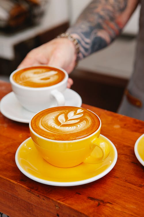 Crop anonymous tattooed male employee serving delicious coffee with ornament on foam in ceramic cups in cafe