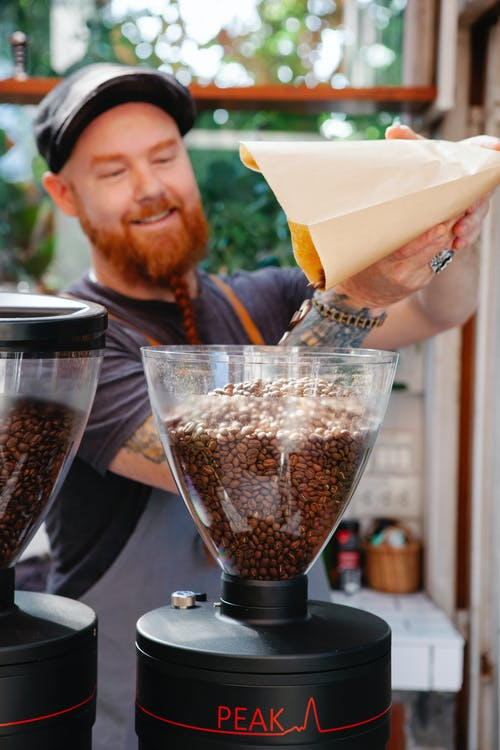 Content adult bearded male cafe worker pouring coffee beans from paper bag into professional grinder in kitchen