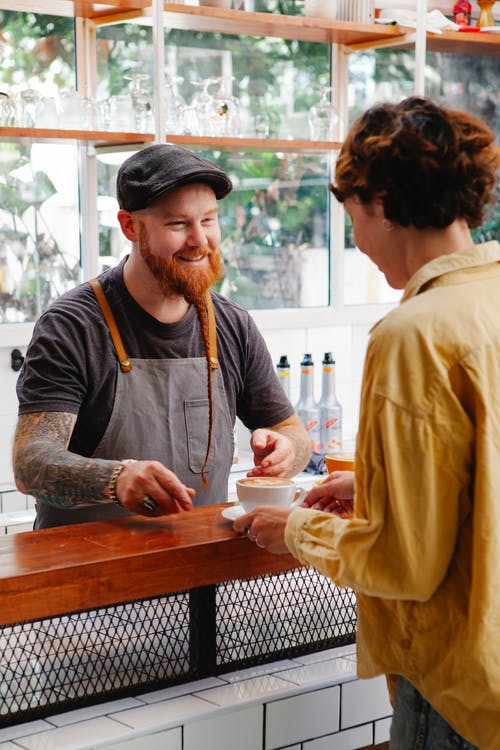 Cheerful hipster barista talking to colleague with coffee at counter