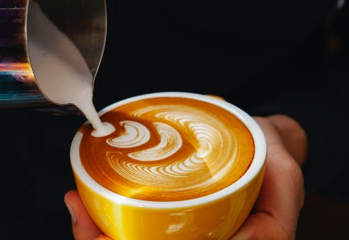 Crop barista pouring milk into coffee with foam in cafe