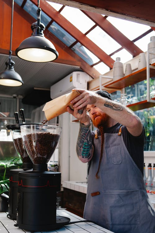 Adult tattooed male employee pouring aromatic coffee beans from paper bag into electric grinder in cafe kitchen