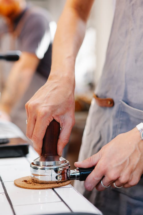 Faceless barista tamping coffee in portafilter in cafe kitchen