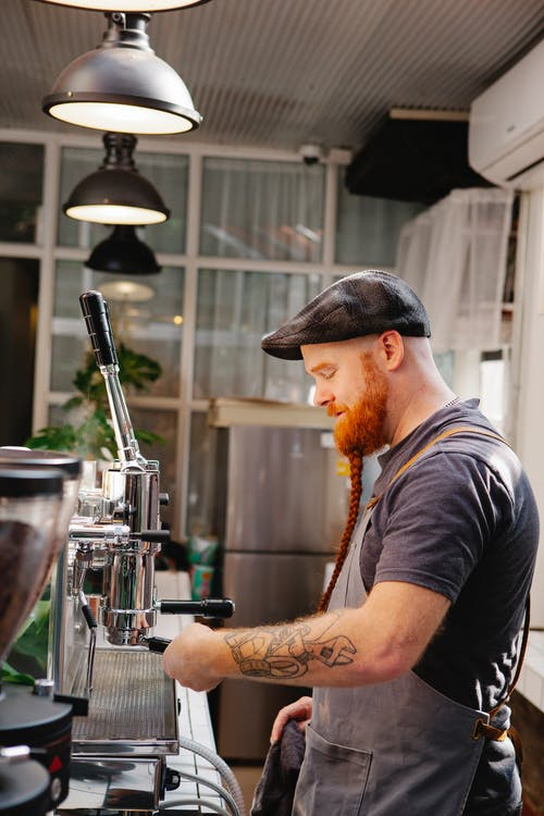 Side view of adult bearded male employee inserting portafilter into professional espresso maker in coffee shop