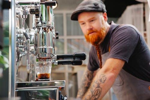 Hipster barista against coffee maker brewing espresso in kitchen